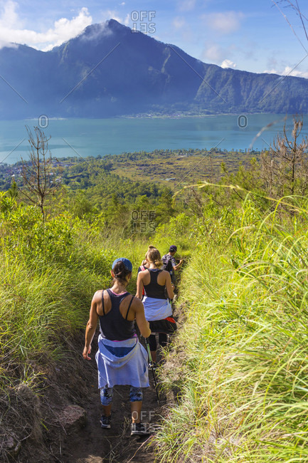 Rear View Of Hikers Hiking In Grass Field Of Bali Island