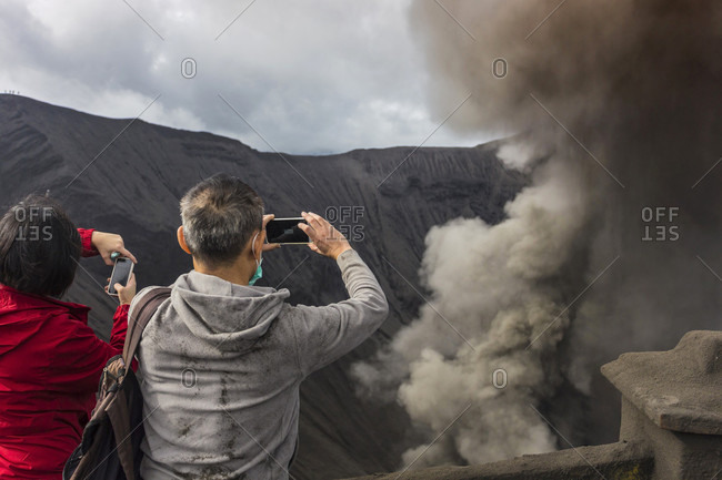 Hikers Standing On Top Of The Mountain And Taking A Pictures Of Geothermal In Java, Indonesia