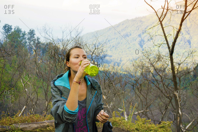 Young Female Hiker Drinking Water At Mountain Valley