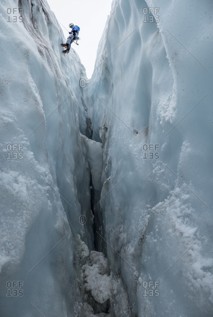 Man Rappelling Into A Crevasse On The Colman Glacier On Mount Baker