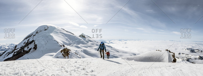 Two Climbers On The Summit Of Colfax Peak With Mount Baker In Background