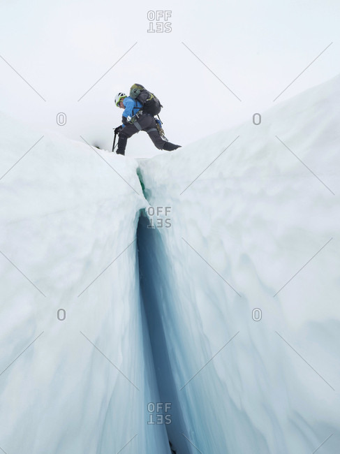 Climber Steps Over A Crevasse On The Coleman Glacier On Mount Baker