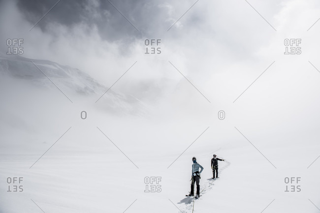 Two Climbers On The Ruth Glacier Navigating In Low Visibility Conditions