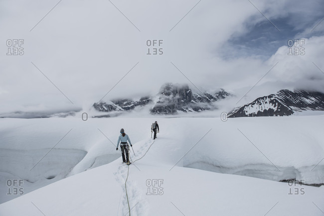 Two Climbers Hiking In Crevasses On The Ruth Glacier In Denali National Park