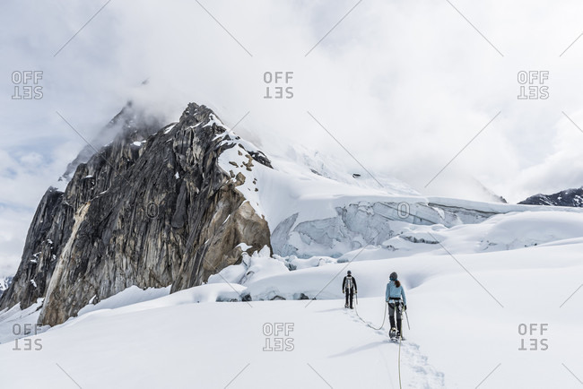 Two Climbers Walking Through Crevasses On The Ruth Glacier In Denali National Park