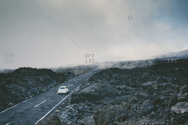 A Car Riding On A Misty Road Surrounded By Volcanic Rocks