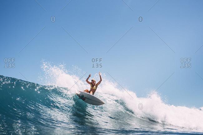 A Girl Surfboarding On A Wave In A Bikini In La Gomera