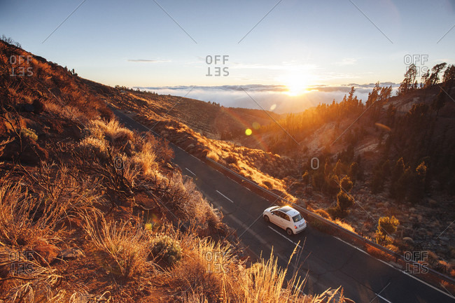A Car Riding On An Empty Mountain Road During Sunset