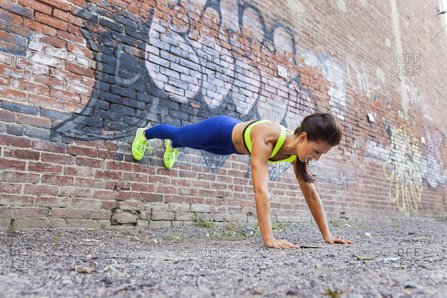 Woman Doing Push Up Against Brick Wall