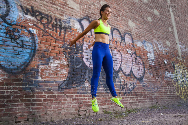 Smiling Woman Doing Exercise Against Brick Wall