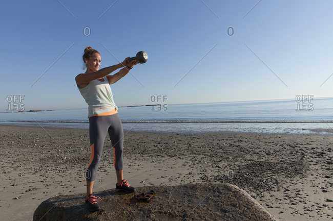 Woman Working Out On The Beach With Weights