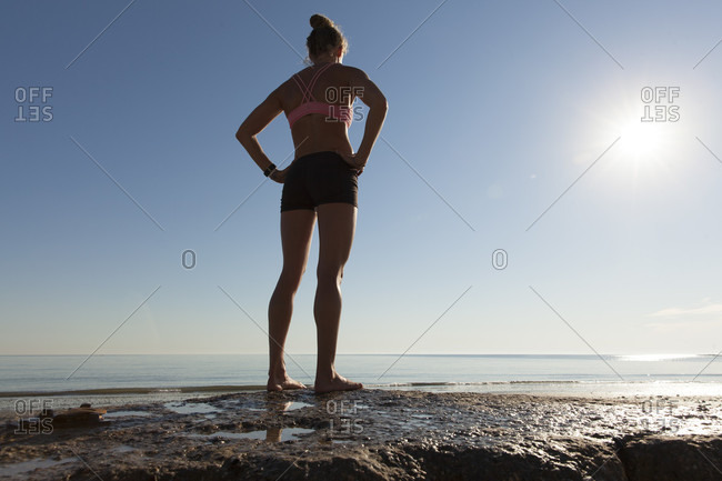 Rear View Of Athlete Woman Standing On Beach