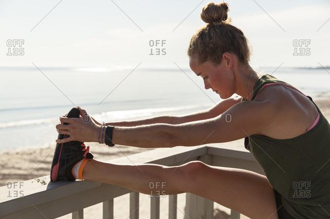 Woman Doing Stretching On Balcony Near Beach