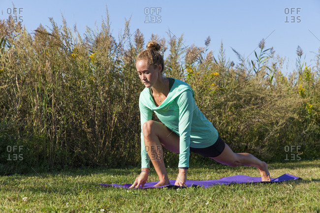 Young Woman Doing Yoga On Grass