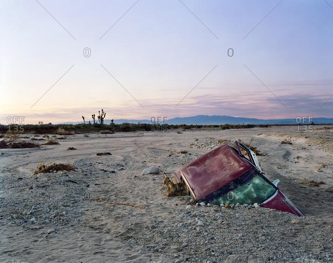Car half buried in desert