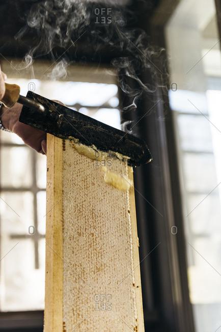 Heated knife cutting through honeycomb to harvest honey