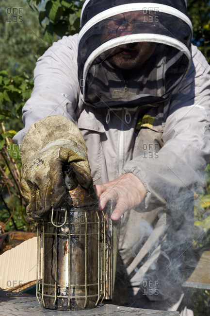 Beekeeper adjusting the smoker he uses to calm his honeybees
