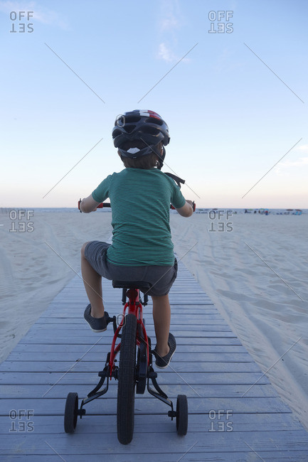 Boy riding bike on beach boardwalk at dusk