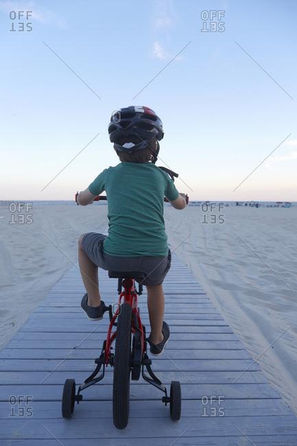 Boy riding bike on beach boardwalk at dusk