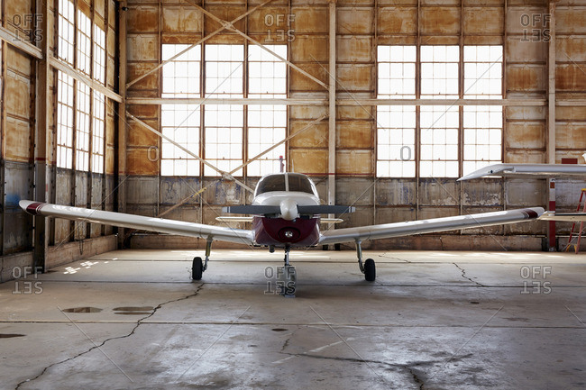 Small propeller airplane in hanger
