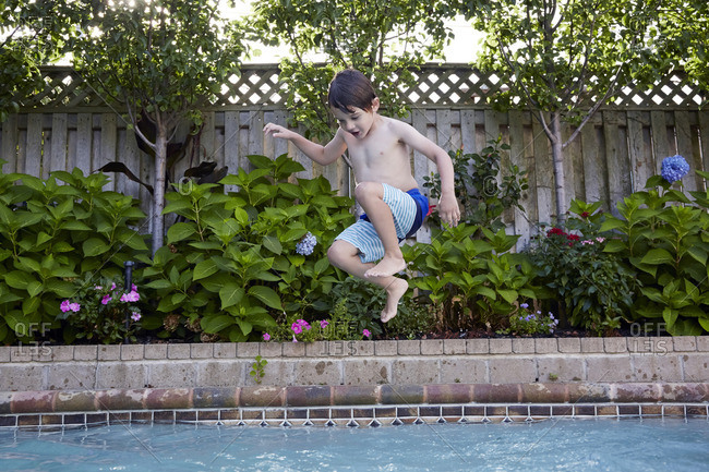 Young boy jumping into swimming pool
