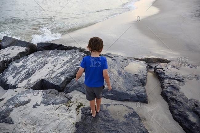 Young boy walking on rocks at beach