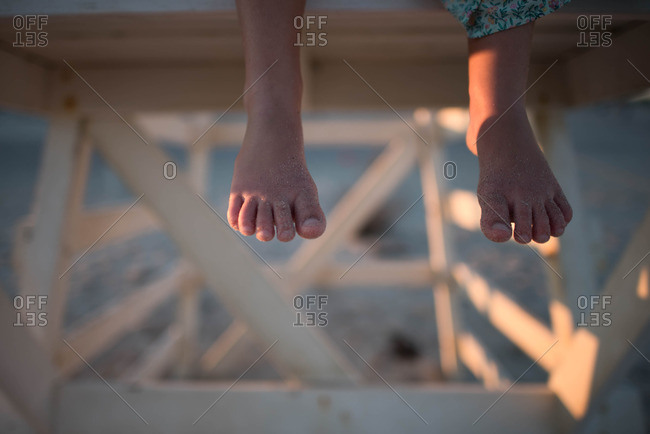 Child's bare sandy feet dangling from lifeguard stand