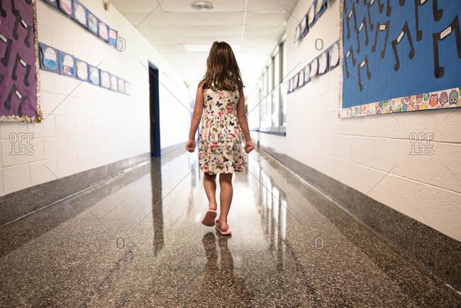 Young girl walking down hallway of elementary school