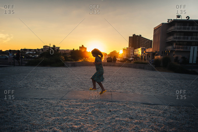 Young girl skipping on beach sidewalk at sunset