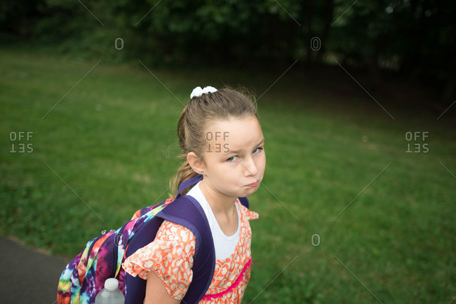 Girl in backpack making a sad face