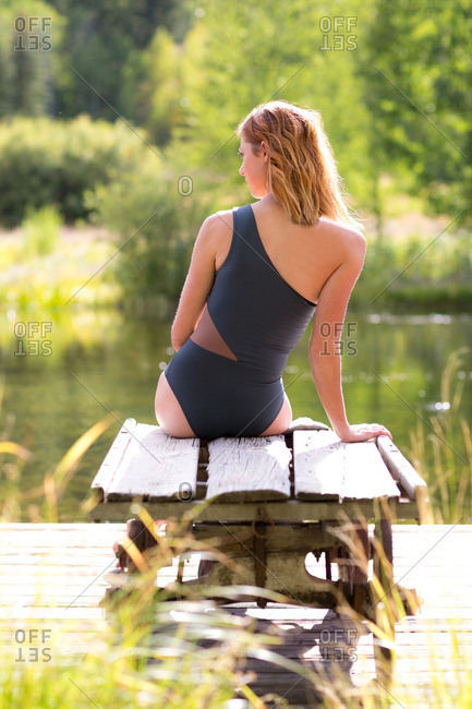 Woman in swimsuit sitting on bench at water's edge