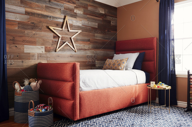 August 15, 2016: Bed by a wood panel wall