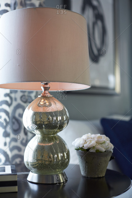 A lamp and flowers on table