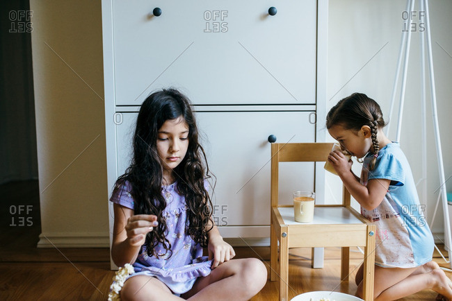 Two young girls stringing popcorn and drinking eggnog