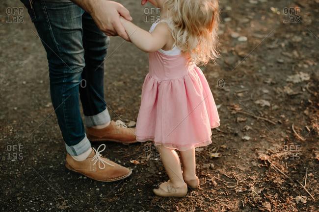 Man holding girl's hands in sunlight