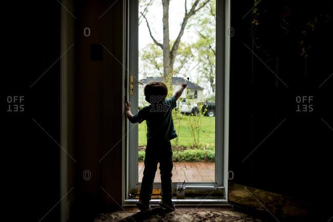 Boy painting on glass door