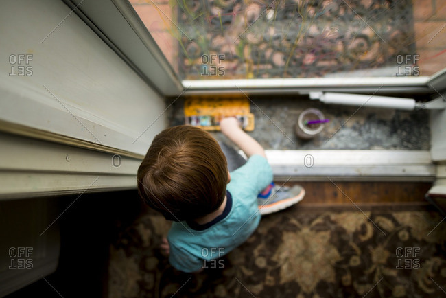 Boy painting by glass door