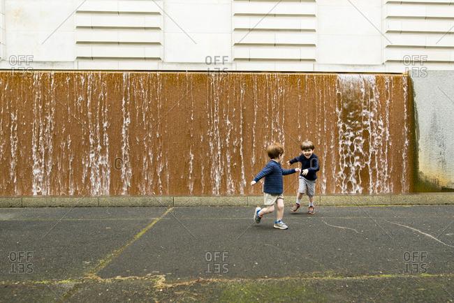 Boys running around a plaza
