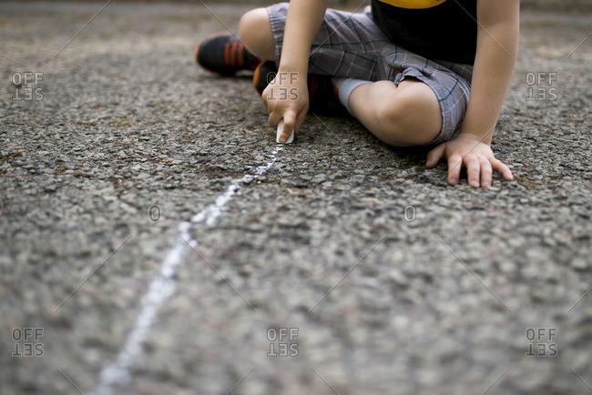 Child drawing line on pavement