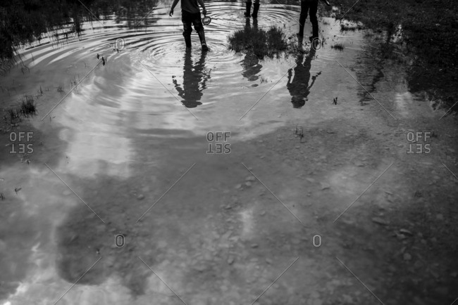 Kid's reflections in a puddle