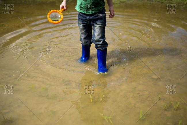 Boy exploring in a wet field