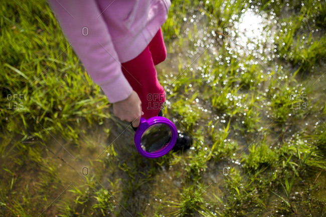 Girl with magnifying glass in field