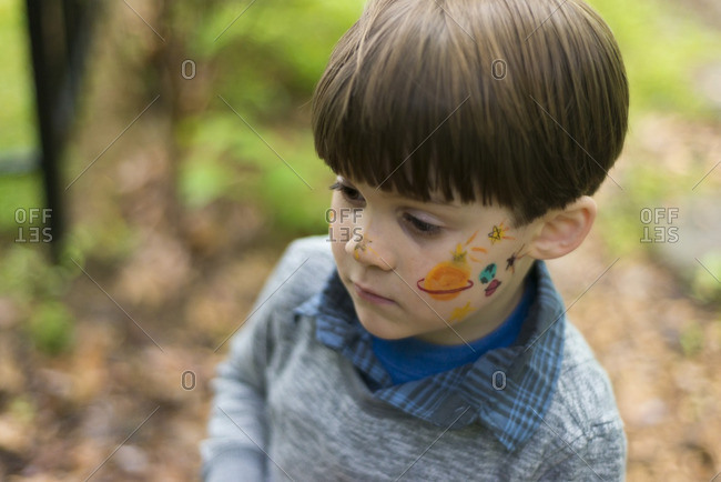 Boy with face painted in yard