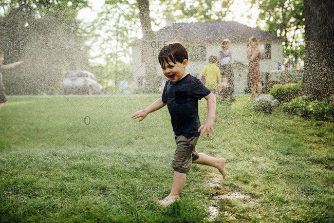 Boy in a sprinkler in front yard