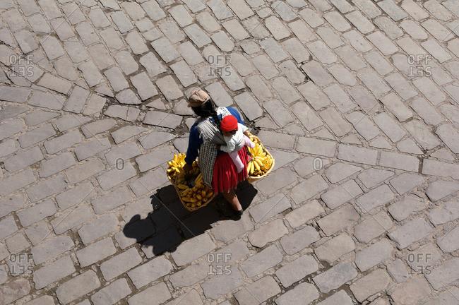 Ecuador, Cuenca - April 29, 2005: Ecuadorian woman with child and bananas