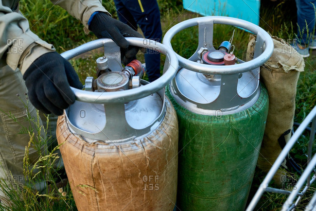 Hot air balloon pilot turning propane cylinder valve to inflate the balloon
