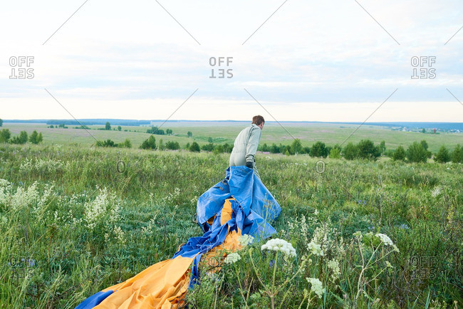 Man pulling air balloon on a green field