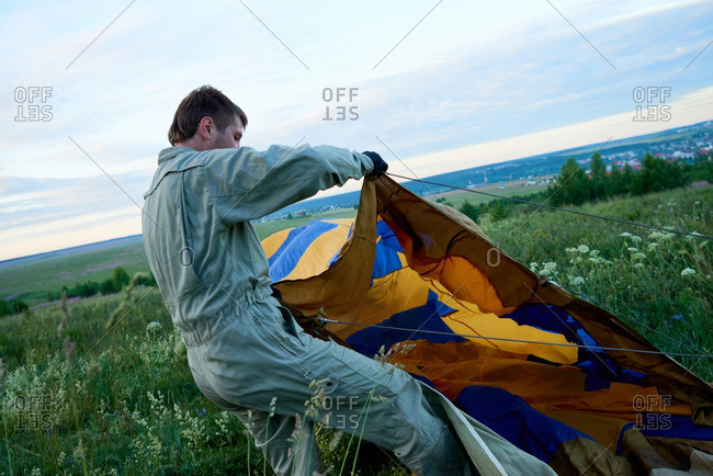 Man pulling air balloon to inflate it