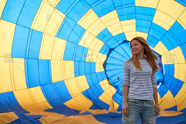 Young girl standing against inflating hot air balloon