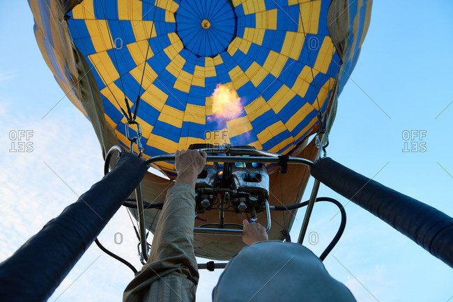Man inflating hot air balloon with gas burner